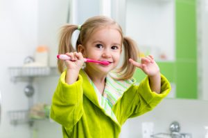 girl brushing teeth in bathroom